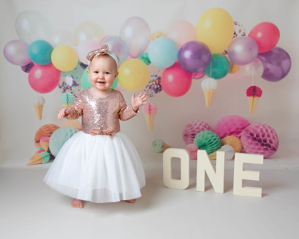 Baby girl in colourful balloon set during 1st Birthday cakesmash photoshoot in Glasgow