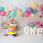 Happy 1st Birthday, lovely colourful balloons & baby girl eating cake during cakesmash photoshoot in Haywards Heath