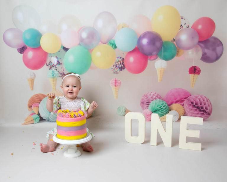 Happy 1st Birthday, lovely colourful balloons & baby girl eating cake during cakesmash photoshoot in Haywards Heath