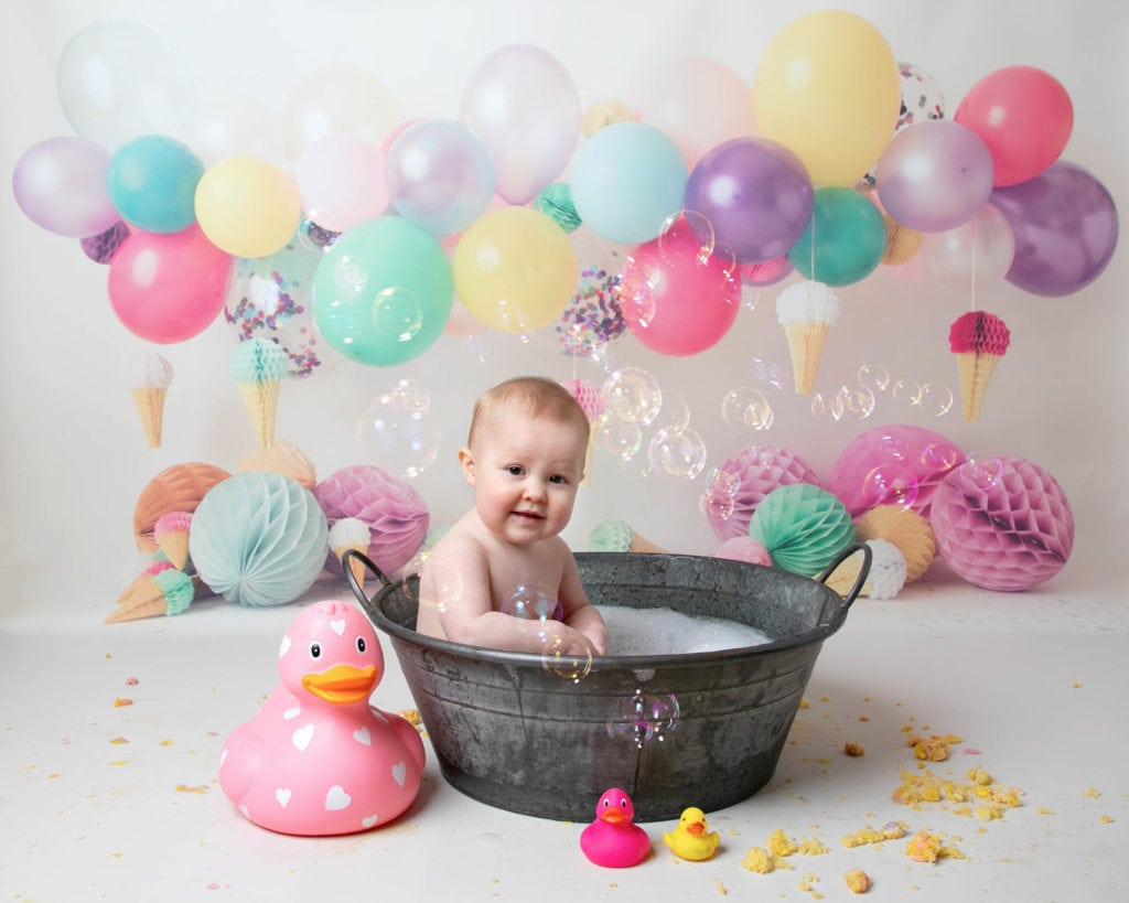 Baby girl in bath with bubbles & balloon backdrop during 1st birthday cakesmash photoshoot in Glasgow