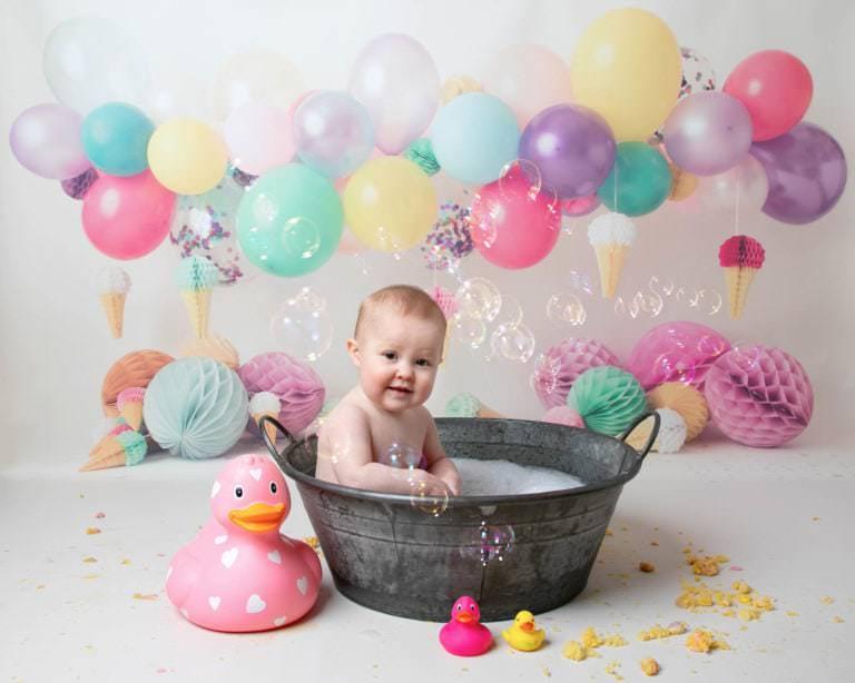 Baby girl in bath with bubbles & balloon backdrop during cakesmash photoshoot in haywards heath