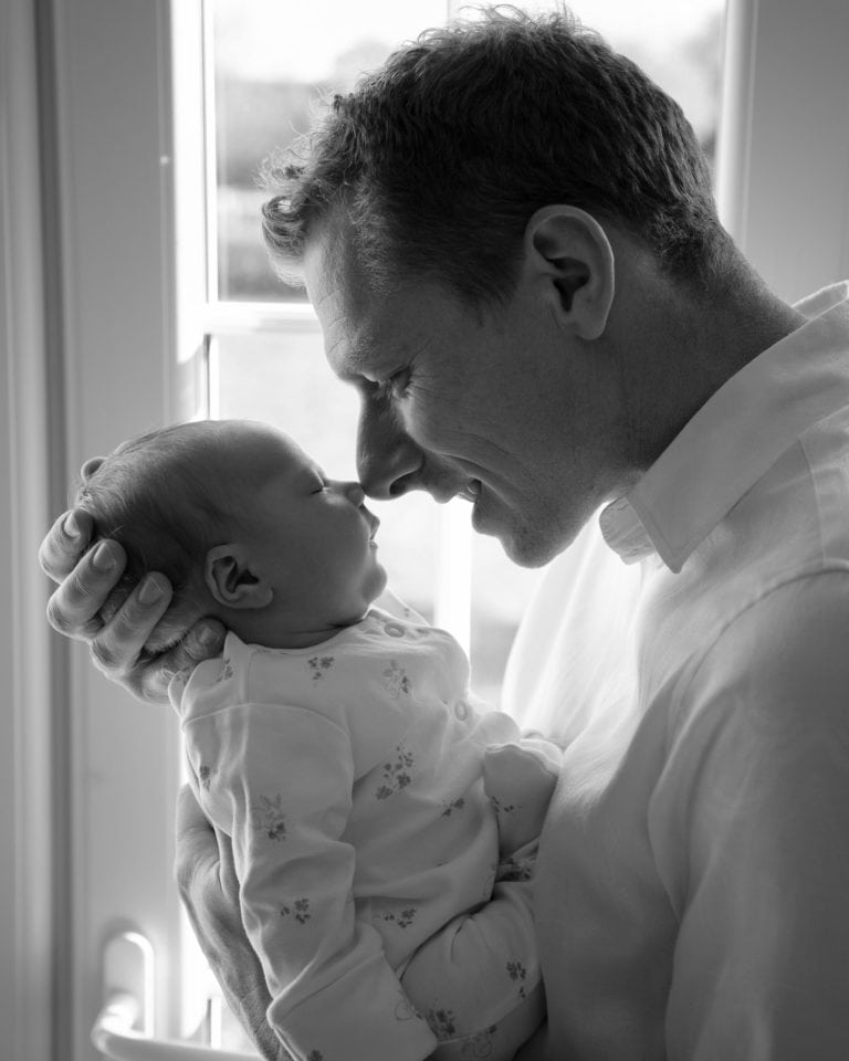 Black & White image of dad rubbing noses with baby by Haywards Heath photographer