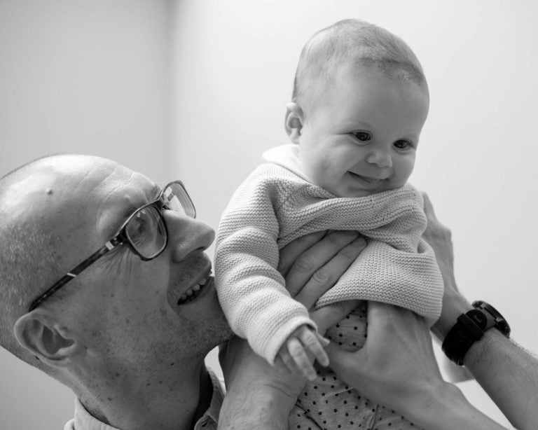 Daddy holding baby girl up smiling down at mummmy by haywards heath photographer