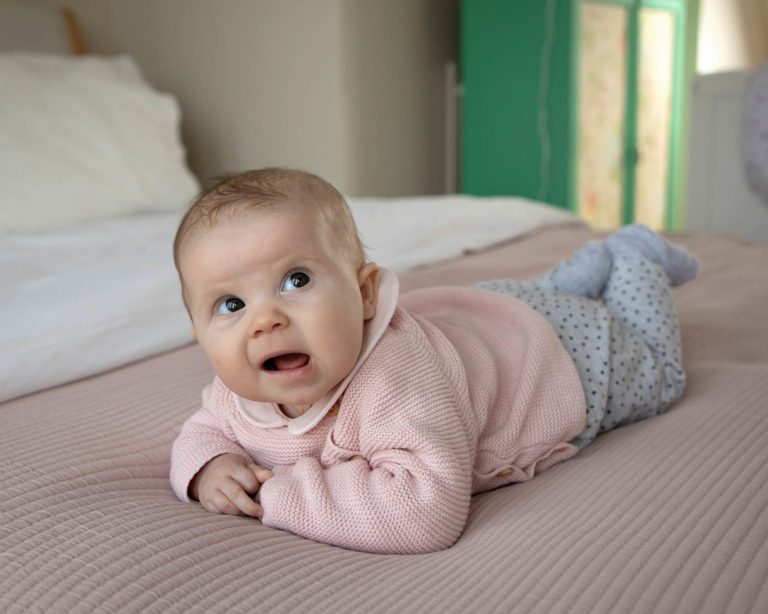 Baby girl lying on front o bed by haywards heath photographer