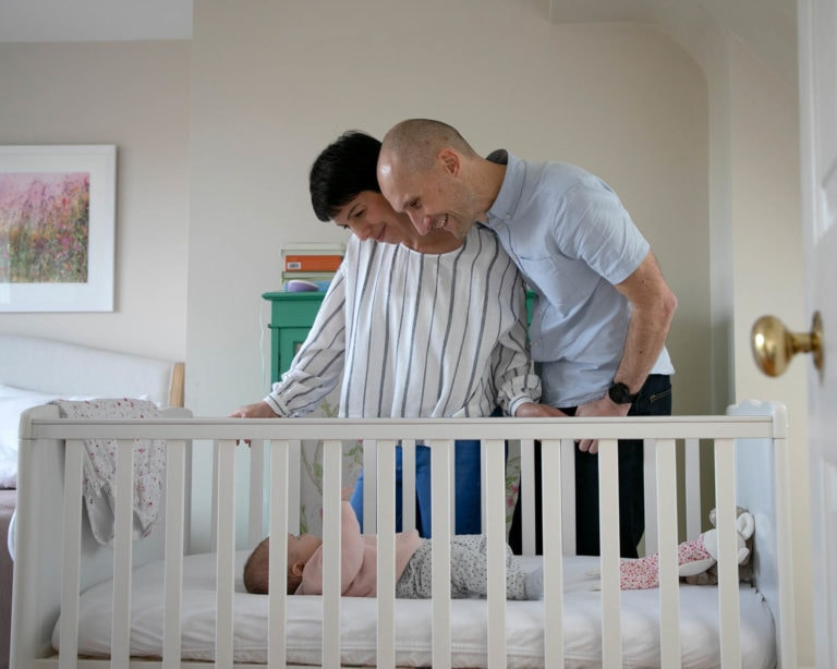 Haywards Heath photographer captured parents lookings into cot at baby