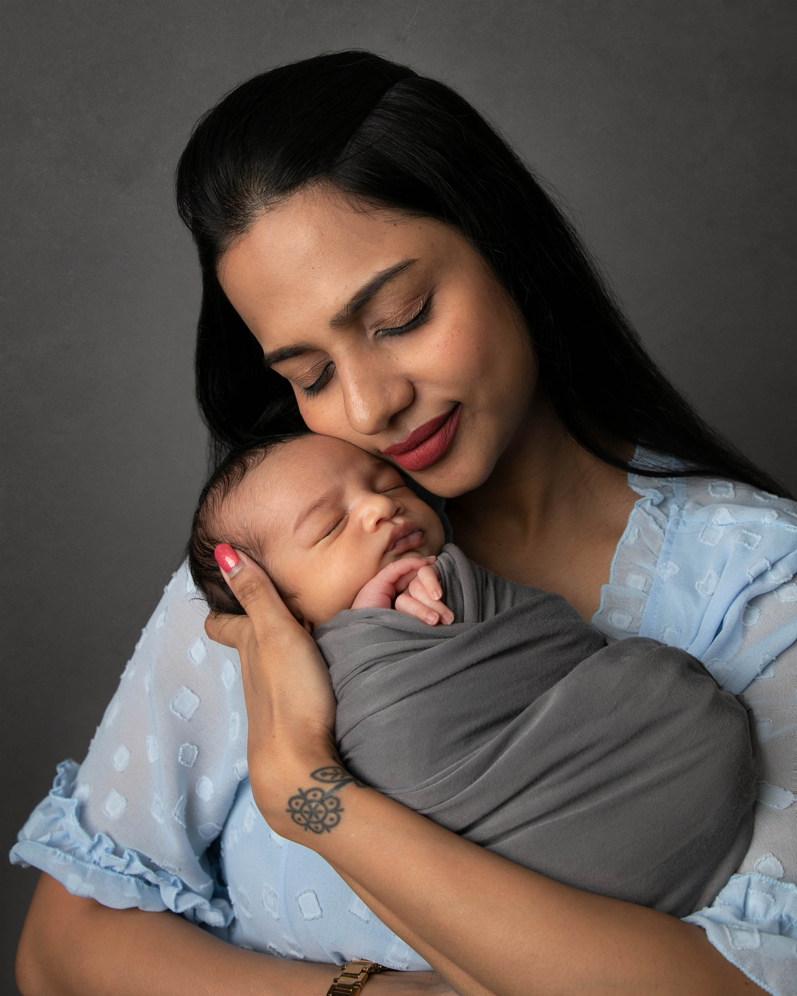 Mum holding newborn baby close with her eyes closed by haywards heath photographer