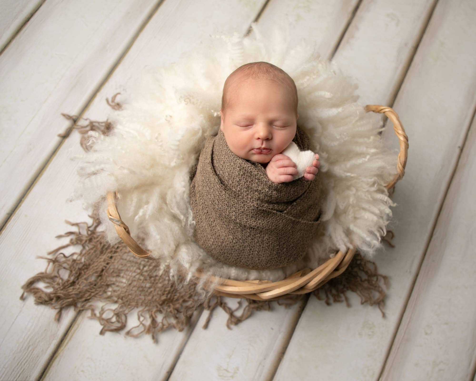 Baby boy wrapped in brown fabric, in a basket with cream fur and holding a cream heart. Image taken from above during Glasgow Baby Photoshoot