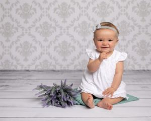 Little baby girl wearing white dress, sat on grey wooden backdrop with wallpaper background. Baby has a bunch of lavender by her side and is smiling at the camera doing her older baby photoshoot
