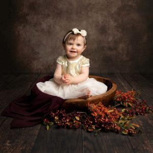 Baby girl sat in brown bowl with autumnal berries around her. Girl wears a cream dress with a cream bow headband. Image taken during baby photoshoot in Glasgow