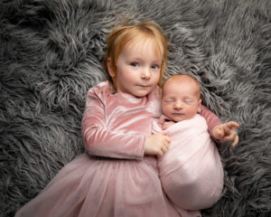 Girl with baby sister both in pink on a grey flokatti. Part of a gallery from newborn photography shoot in Glasgow