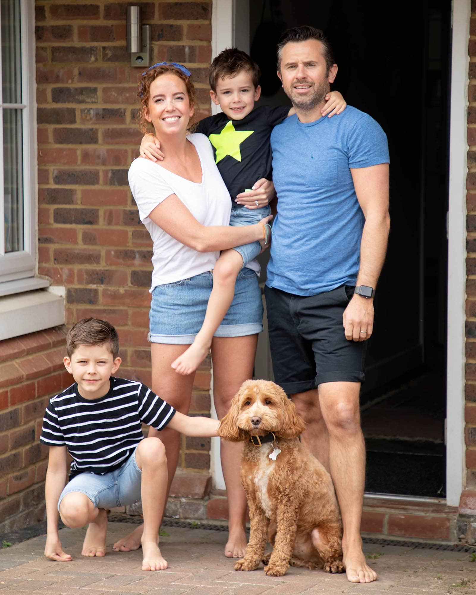 doorstep portrait family with 2 young boys and dog stood outside their house during photoshoot in haywards Heath