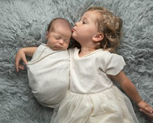 Baby with sibling, both in white on a grey flokatti. Close up of baby boy in blue at newborn photoshoot