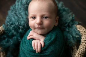 Baby boy in green, in a basket, smiling with his eye open. Part of a gallery from newborn photography shoot in Glasgow