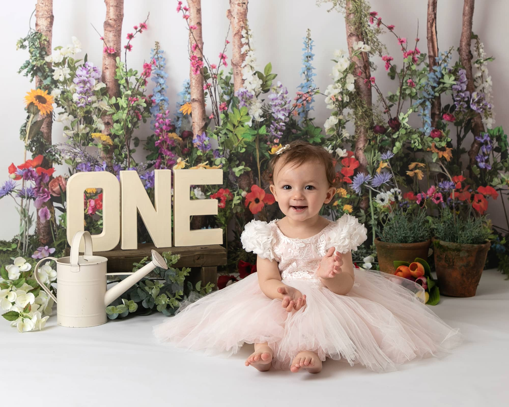 Glasgow photographer cakesmash photoshoot for 1st birthday. Little girl in pink tulle dress sat in front of a floral meadow scene with one letters on background