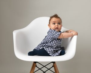 Baby girl in blue gingham dress sat in cream hermes chair looking at photographer takin her image for a baby photoshoot in Glasgow