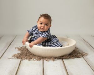 Baby girl in blue & white gingham dress sat in a cream bowl, leaning to the side and looking forward. Baby is having a photoshoot with Glasgow photographer