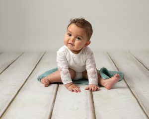 8 month old baby sat on a cream wooden floor on a small blanket wearing a white long sleeve romper. Taken by Glasgow Baby Photographer Louise Ferguson