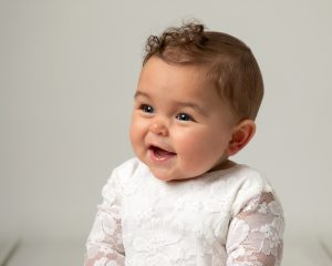 Baby girl with short curls wearing a white romper smiling. Image taken at Glasgow baby photography shoot