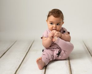 Baby girl with short brown curls wearing a pink romper with blue stars sitting on a cream wood effect backdrop. baby is taking part in a photography session in Glasgow. Toes in hand and in mouth