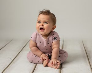 Baby girl smiling at her parent in a baby photoshoot in Glasgow. Girl wears a pink romper with blue stars