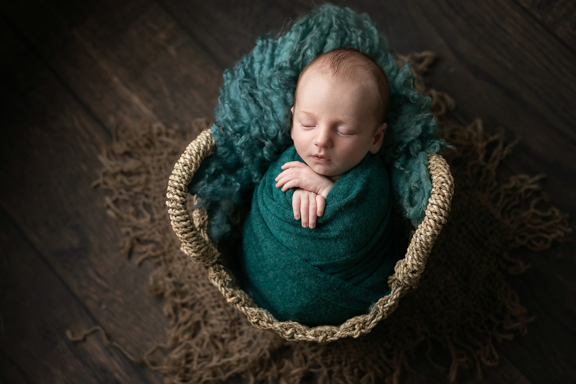 Baby boy wrapped in jade green in a basket on green fur, sat on dark wooden floor. Picture taken by Glasgow photographer