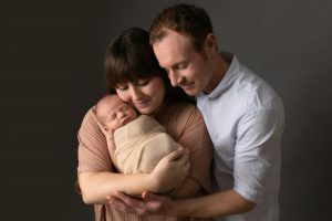 Parents with baby. Mum in pink top, baby wrapped in cream fabric, dad wearing blue shirt. Image part of newborn photography session in Glasgow