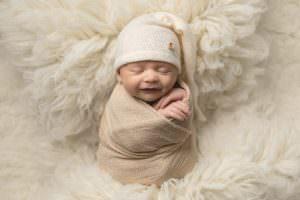 Baby boy swaddled in cream wrap on cream fur flokatti, wearing a cream sleepy hat.