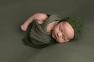 Baby boy wrapped in Green on matching fabric posed on his back with legs out. Matching green bonnet. Image part of newborn photography session in Glasgow