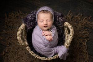 Baby girl swaddled in a lilac wrap and wearing a matching bonnet in a rattan basket. Image taken from above with baby looking upwards. Part of a newborn photography session in Glasgow