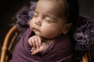 Baby wrapped in purple, close up sleeping with hands crossed. Image part of newborn photography session in Glasgow