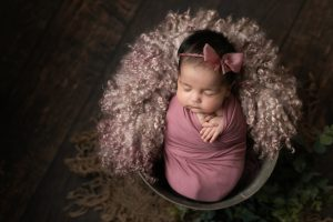 Baby girl wrapped in deep pink fabric wearing pink bow halo, posed in bucket. Image part of newborn photography session in Glasgow