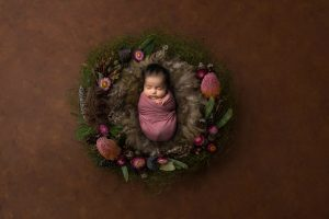 Baby wrapped in pink and posed in floral wreath with brown fur. Image taken from above