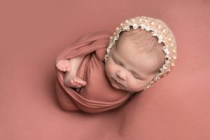 Baby girl on dusky pink backdrop swaddled in wrap of same collier with feet showing. Baby wears a pink bonnet.Image captured during newborn photography session in Glasgow