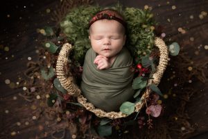 Baby girl swaddled in green wrap, in a wicker basket on a dark wood floor. Baby is resting against a green woven blanket with festive greenery wrapped around the basket. Image part of a newborn photography session in Glasgow, with festive styling.