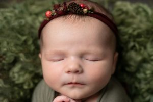 Baby girl wearing festive halo on green curls. Image taken straight on and close up. Image part of newborn photography session in Glasgow