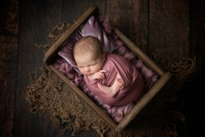 Baby posed in wooden bad wrapped in deep pink fabric.