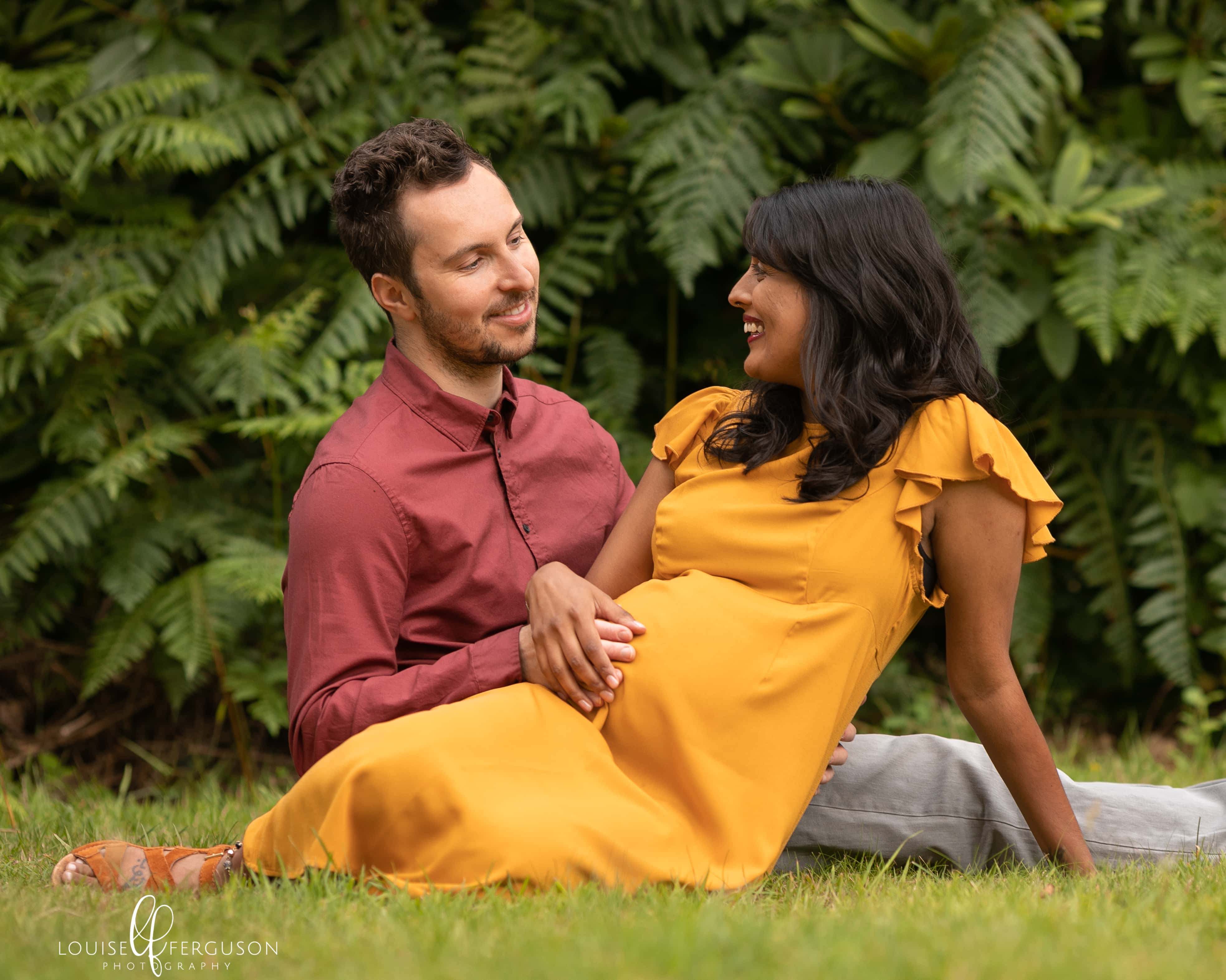 Couple sat outdoors, female wearing a ochre coloured dress, male wearing a rust coloured shirt and beige chinos. Couple are sat on grass with tall ferns behind. Female is pregnant. Image taken during pregnancy photoshoot in a Glasgow beauty spot