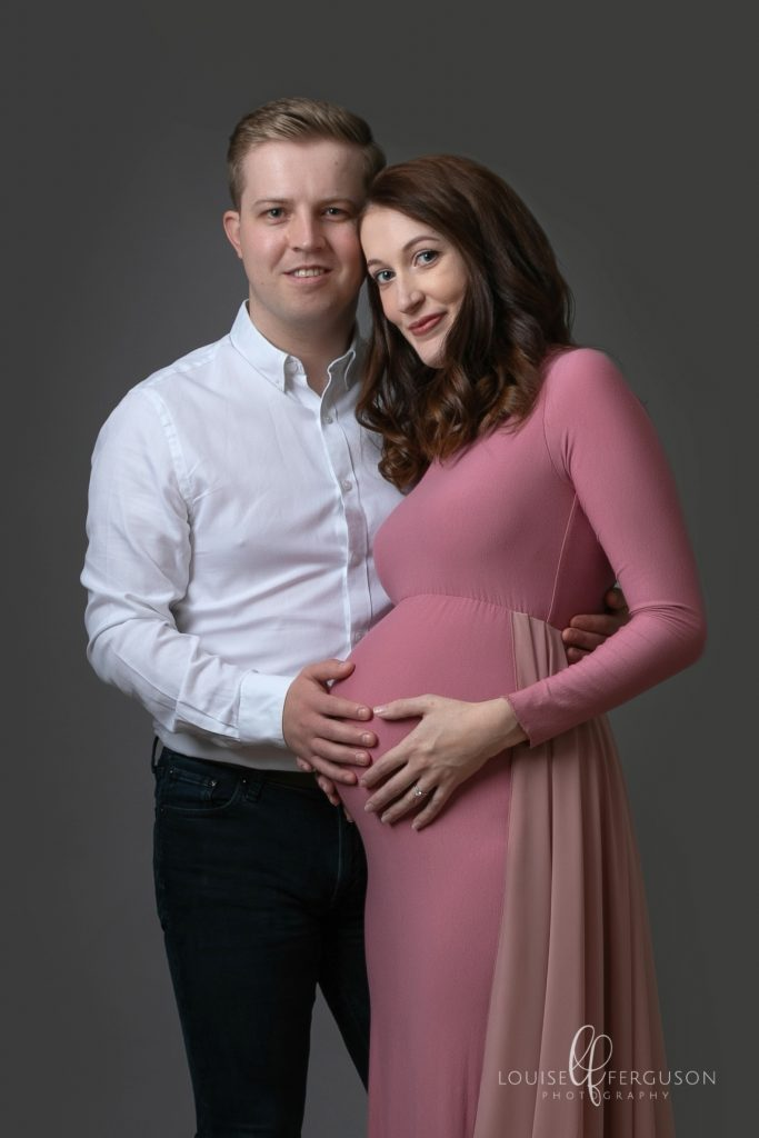 Male & female. Female is pregnant wearing a pink maternity at her pregnancy photoshoot in Glasgow
