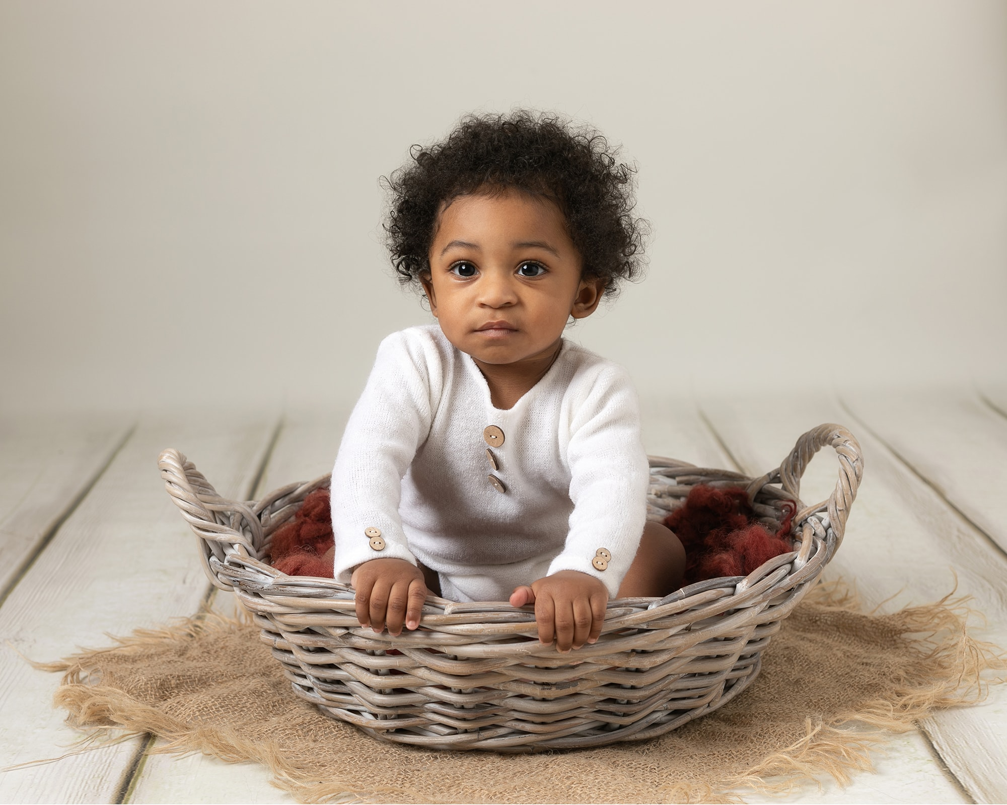 Baby boy wearing white rompers sat in a cream bowl on brown fluff, leaning forward looking at the camera. Image taken by award winning baby photography in Glasgow