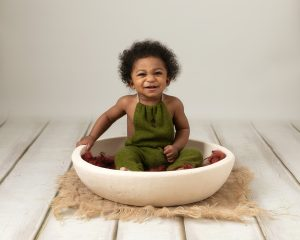 Baby boy sat in a cream bowl on a cream backdrop. Boy wears green dungarees and is smiling. Image taken during baby photography shoot in Glasgow