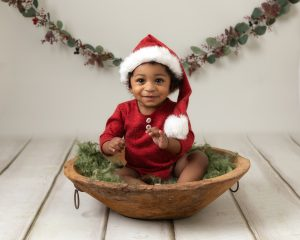 Baby boy in a red romper with a sant hat on sat in a brown wooden bowl on top of green fluff. Cream backdrop with xmas garland hanging behind. Boy is smiling for photographer taking images at a baby photography session in Glasgow