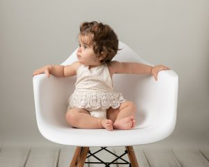 Baby girl sat on white here's chair wearing a pink chiffon dress. Baby is giggling as she takes part in her baby photography session in Glasgow