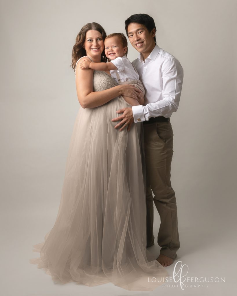 Image taken by Maternity Photographer in Glasgow. Male & female with male toddler. Female is pregnant and wearing a cream gown with tulle skirt, She is holding toddler on her bump and male has his arms around her. Male wears a white shirt & chinos