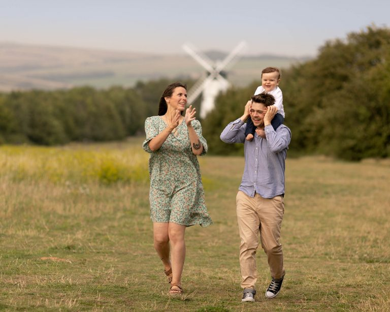Couple walking in the countryside. dad has baby pn his shoulders. A windmill can be seen in the background. Image taken during a family photography session in Glasgow