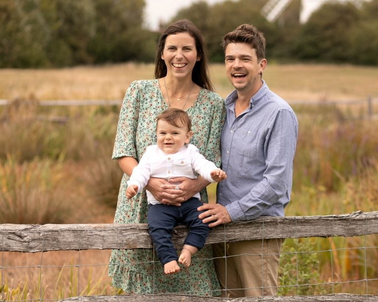 Family with baby sat on a fence during family photography session in Glasgow outdoor photoshoot in countryside