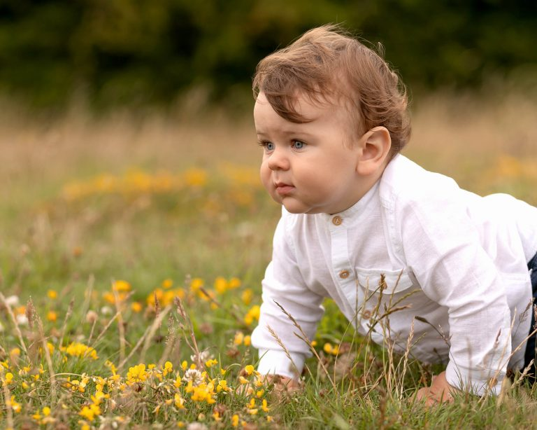 Baby boy crawling in flowers & grass during outdoor family photography session in Glasgow