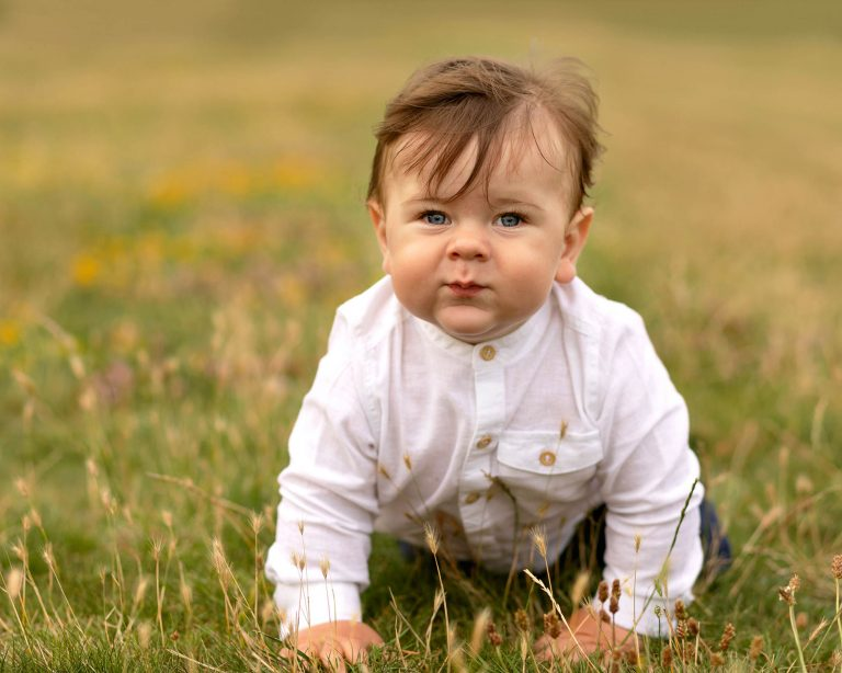 Baby boy crawling in long grass and flowers during family photography session in Glasgow