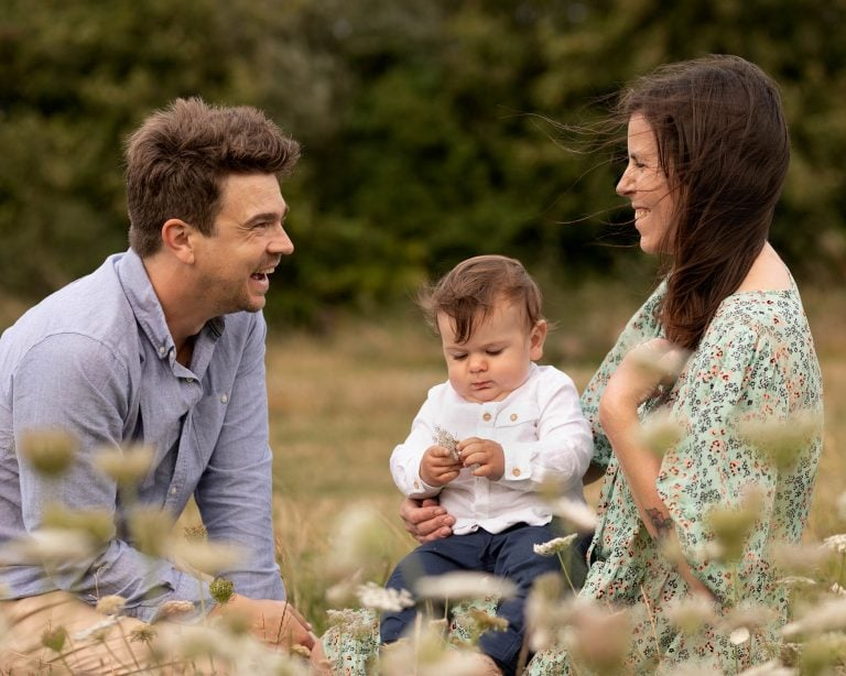 Parents sat laughing with each other whilst baby plays in outdoor location. Image part of family photography portfolio in Glasgow