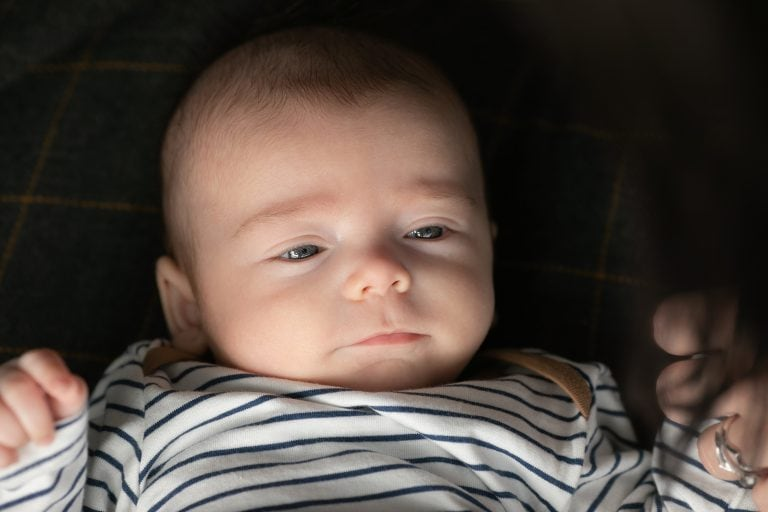 Baby boy lying on a rug. Close up of face during outdoor family photography session in Glasgow