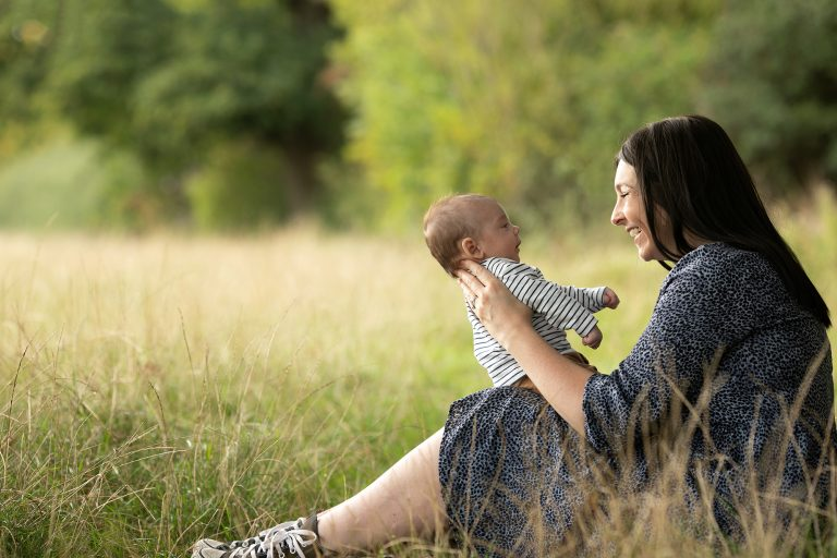 Mum holding baby boy, facing her and smiling at him. Image taken outdoors during a family photography session in Glasgow